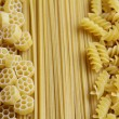 Three types of uncooked (raw) pasta (macaroni): spaghetti, fusilli and fiori - Stock Photo