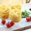 Composition made in colours of Italian flag: three portions of raw tagliatelle pasta along with cherry tomatoes and herbs on a cutting board — Stock Photo