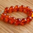 A close-up shot of a fluorescent amber bracelet shining in the sunlight - Stock Photo