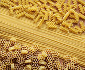 Three types of uncooked (raw) pasta (macaroni): spaghetti, fusilli and fiori — Stock Photo