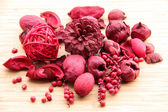 A red berry and fruit potpourri composition against a wooden background — Stock Photo