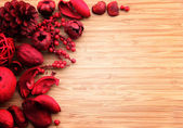 A red berry and fruit potpourri composition against a wooden background with copy space — Stock Photo