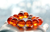 A close-up shot of a fluorescent amber bracelet shining in the sunlight — Stock Photo