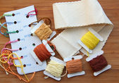 Cross-stitch set: colour palette, threads, canvas against a wooden background — Stock Photo