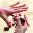 Stock Photo: A female is trying three different shades of lipstick on her hand to see which matches the skin colour when shopping for makeup
