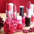 A collection of makeup: lipsticks, lipgloss and nail polishes decorated with red potpourri all in red and pink shades isolated on white — Stock Photo #14090173