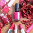 A collection of makeup: lipsticks, lipgloss and nail polishes decorated with red potpourri all in red and pink shades isolated on white — Stok fotoğraf
