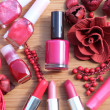 Stock Photo: A collection of makeup: lipsticks, lipgloss and nail polishes decorated with red potpourri all in red and pink shades isolated on white