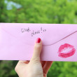 Female hand holding a pink envelope with a red lipstick kiss print and copy space — Stock Photo