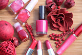 A collection of makeup: lipsticks, lipgloss and nail polishes decorated with red potpourri all in red and pink shades isolated on white — Stock Photo
