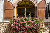 Itterswiller (Alsace) - Flowered window with wine bottles — Stock Photo