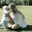 Baby funning with mother on the grass in park — Stock Video