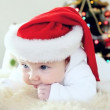 Baby in Christmas hat on the new year background - Stok fotoraf