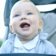 Smilling baby sitting outdoors - Stok fotoraf