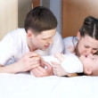 Happiness family: father, mother and baby playful on the bedroom - Stockfoto