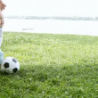 Baby with father playing with soccer ball on the grass - Stockfoto