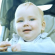 Smilling baby sitting outdoors - Stockfoto