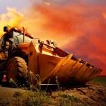 Yellow tractor on golden surise sky — Stock Photo #6355529