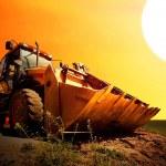 Yellow tractor on golden surise sky — Stock Photo #6355538