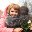 Happy young woman with flowers embracing man — Stock Photo