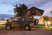 Jipe safari com uma barraca do telhado em um local de acampamento — Foto Stock
