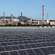 Solar power station with a oil refinery in the background — Stock Photo