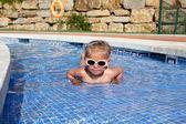 Little girl with sun glasses having fun in the pool — Stock Photo