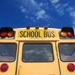 Yellow school bus against blue sky — 图库照片
