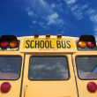Yellow school bus against blue sky — Stock fotografie