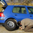 Man changing a tire on the road — Stock Photo