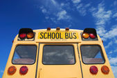 Yellow school bus against blue sky — Stock Photo