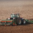 Tractor ploughing field in autumn — ストック写真