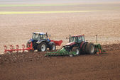 Two Tractors ploughing field in autumn — Stock Photo