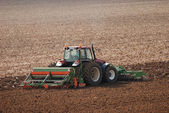 Tractor ploughing field in autumn — Stock Photo