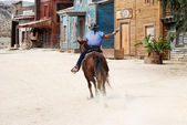 Cowboy on horseback shooting and riding away — Foto de Stock