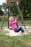 Happy toddler girl on a swing in city park — Stock Photo