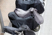Covered motorcycles parked in the street — Stock Photo