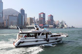 Motor yacht with tourists cruising in the harbour of Hong Kong — Stock Photo