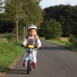 Little girl riding her training bike outdoors — Stock Photo #51074485