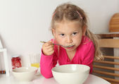 Cute four year old girl eats soup at home — Stockfoto