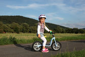 Happy four year old girl on a training bike  — Stock Photo