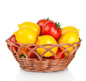 Ripe red and yellow tomatoes in wicker basket isolated on white — Stock Photo