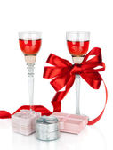 Wine in two wineglasses with red satin bow and gift box isolat — Stock Photo
