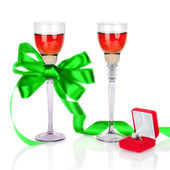 Wine in two wineglasses with green satin bow and wedding rings — Stock Photo