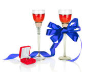 Wine in two wineglasses with blue satin bow and wedding rings i — Stock Photo