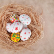 Easter eggs in nest on rustic wooden planks - Stock Photo