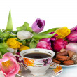 Bouquet of colorful tulips and  tea cup full of tea isolated on - Stock Photo