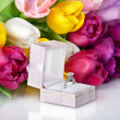 Bouquet of beautiful tulips flowers and wedding ring - Stock Photo