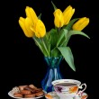 Bouquet of yellow tulips in glass vase and Antique tea cup full — Stock Photo #22379343