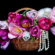 Basket with colorful bouquets of tulips flowers on black backgro - Stock Photo